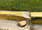 A yellow curb with a large piece of concrete missing