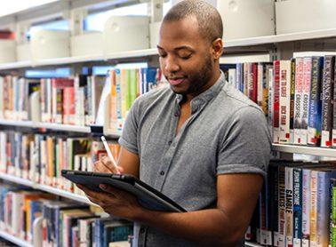 Man next to bookshelves using a tablet