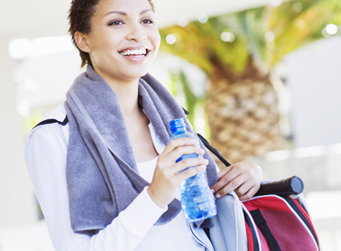 Smiling woman with a water bottle, towel and gym bag