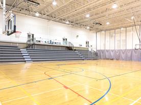 Interior of empty gym showing bleachers