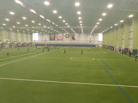 People playing soccer on indoor field