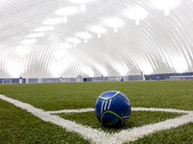 Blue soccer ball sitting in corner of covered sports field