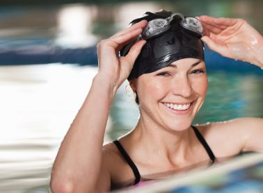 Young woman in pool lifting up swim goggles